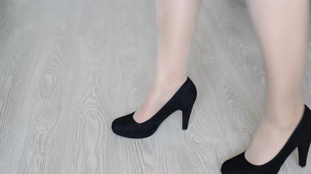 volno : Woman takes off down a black high-heeled shoes