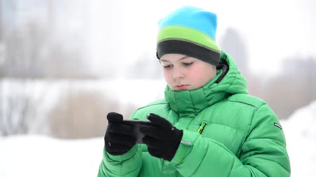 telefon : boy uses a cell phone with gloves outside in winter