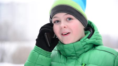 telefon : Boy talking on a cell phone outside in winter