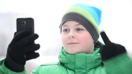 telefon : boy uses cell phone with touchscreen gloves outside in winter Stock mozgókép