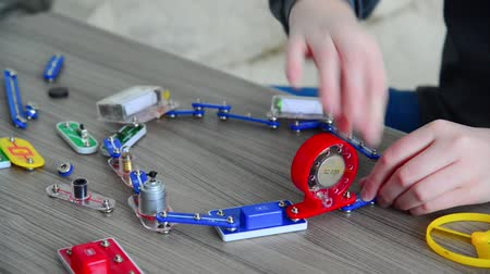kísérlet : Boy assembles the electrical circuit from constructor Stock mozgókép