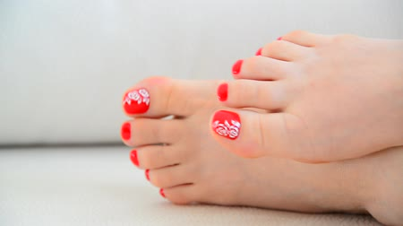 polonês : Female feet with red nail polish and floral pattern Vídeos