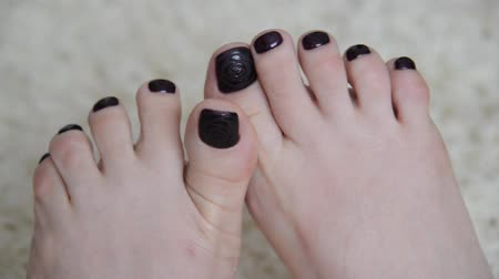 polonês : Female feet with a dark paint on nails