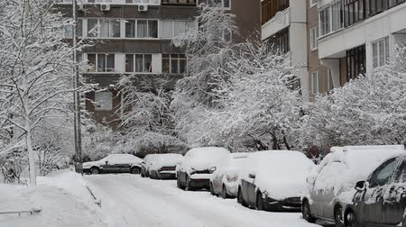 rüzgârla oluşan kar yığını : Row of snow-covered cars along the sidewalk near house. Moscow, Russia Stok Video