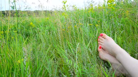 toes : Female legs with a red pedicure on green grass