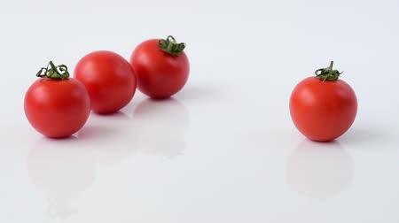 few : Tomatoes roll on white background in slow motion Stock Footage