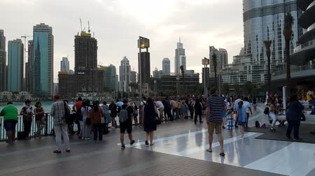 takes : Dubai, UAE - April 8. 2018. Tourists on square at front of Dubai Mall.