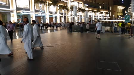 hajtások : Dubai, UAE - April 8. 2018. man of national Arab clothing in square in front of Dubai Mall Stock mozgókép