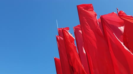 árbocszalag : many Red flags swaying in wind against the blue sky Stock mozgókép