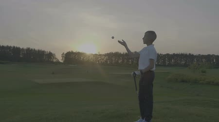 тройник : Junior Golfing Into Sunset.