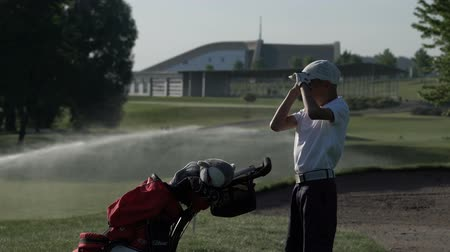 golfjátékos : Junior golfer playing golf on summer with hitting shot on green grass