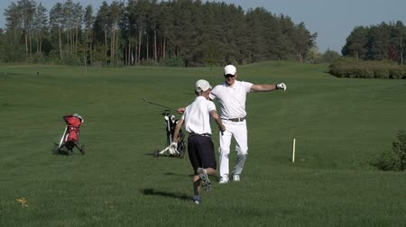тройник : Happy man with his son golfers walking on perfect golf course at summer day