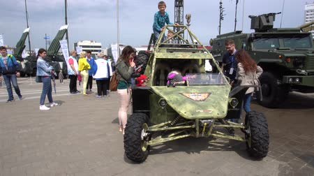 climbed : BELARUS, MINSK, 17 May 2019: 9th International Exhibition of Armament and Military Equipment Milex - 2019. rowd of children climbed onto a machine of military origin, they are learning and playing military equipment