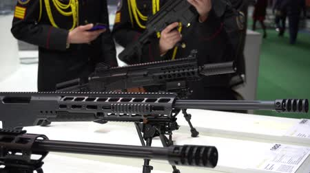 silahlar : BELARUS, MINSK, 17 May 2019: 9th International Exhibition of Armament and Military Equipment Milex -2019. People in military uniform are examining guns at the exhibition booth