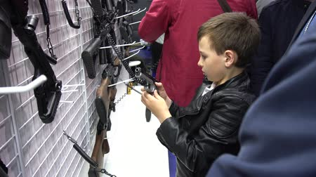 silahlar : BELARUS, MINSK, 17 May 2019: 9th International Exhibition Armament and Military Equipment Milex - 2019. Teen boy examines and tries weapon pistol at exhibition near the stand