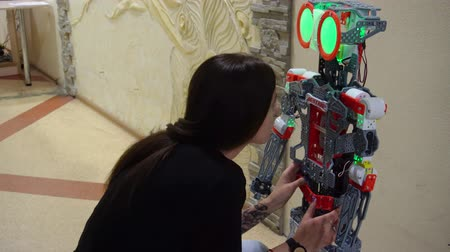 робот : Belarus, Minsk, Robot Exhibition, June 3, 2019: teenager girl communicates with the robot as a friend tells or advises in school class room