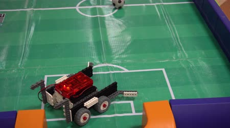 futball labda : Belarus, Minsk, Robot Exhibition, June 3, 2019: RC robotic machines play football on indoor soccer field layout
