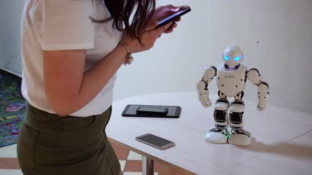 робот : Belarus, Minsk, Robot Exhibition, June 3, 2019: woman controls from the phone sets commands white plastic robot dances on table indoors