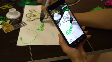Belarus, Minsk, Robot Exhibition, June 3, 2019: girl shoots video on phone as she writes drawings with electronic plastic pen