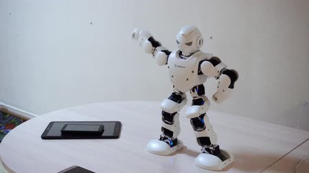 робот : Belarus, Minsk, Robot Exhibition, June 3, 2019: white plastic robot dances on table indoors