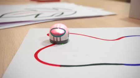 робот : Belarus, Minsk, Robot Exhibition, June 3, 2019: Small robot drives a sheet of white paper along colored lines on a table and glows like a game for children.