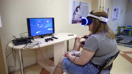 Belarus, Minsk, Robot Exhibition, June 3, 2019: young girl sitting on a chair in the room in front of the monitor wearing glasses of virtual reality plays games racing cars Stok Video