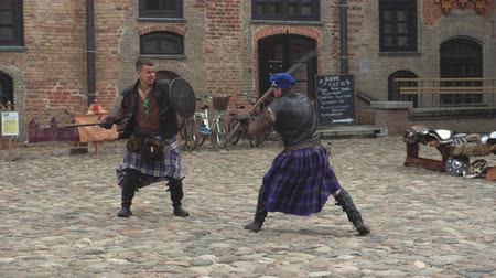 щит : Belarus, the village of Mir, Mir Castle, June 16, 2019: theatrical look at the history of Belarus, a battle with the swords of two men of the Middle Ages, people from Scotland Стоковые видеозаписи