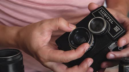 retro revival : Belarus, Soligorsk, July 1, 2019: hands of a male photographer check the performance of an old Soviet wide-format analog film retro camera in a photo studio and focuses