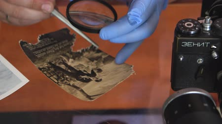 restaurar : Belarus, Soligorsk, July 1, 2019: mastery of restoring old vintage damaged photos of close-up specialist working place with a pair of tweezers with a magnifying glass and gloves
