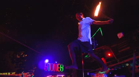 diabolo : Thailand, Phi Phi Island, September 28, 2019: Fire show on open beach. Focused male balancer stands on a rope juggles fireballs at night outdoors