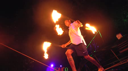 Thailand, Phi Phi Island, September 28, 2019: Fire show on open beach. Focused male balancer stands on a rope juggles fireballs at night outdoors