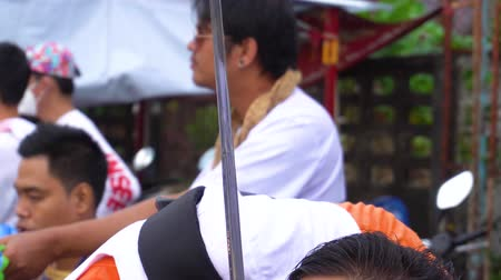imparator : Thailand, Phuket, October 7, 2019: Thai man of Chinese descent with a pierced cheek and tongue pierced by many metal knitting needles at the annual Phuket vegetarian festival Stok Video