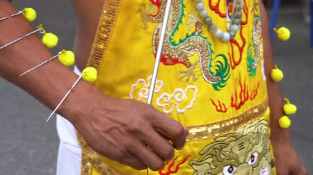 Thailand, Phuket, October 7, 2019: close-up hand of Thai man of Chinese descent with pierced flesh pierced by many metal knitting needles at the annual vegetarian festival in Phuket