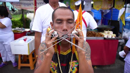 espetos : Thailand, Phuket, October 7, 2019: close-up portrait of Thai man of Chinese descent with pierced cheek pierced by a lot of metal knitting needles at the annual festival of Vegetarianism in Phuket Town