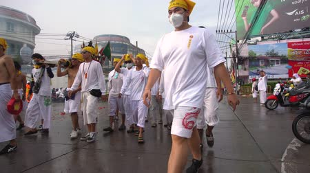 Thailand, Phuket, October 7, 2019: annual Vegetarian Festival nine imperial gods , street procession along the streets of Phuket town near the temple people in white robes with ritual religious accessories Stok Video