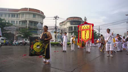 imparator : Thailand, Phuket, October 7, 2019: annual Vegetarian Festival nine imperial gods , street procession along the streets of Phuket town near the temple people in white robes with ritual religious accessories Stok Video