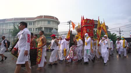 pronikavý : Thailand, Phuket, October 7, 2019: annual Vegetarian Festival nine imperial gods , street procession along the streets of Phuket town near the temple people in white robes with ritual religious accessories Dostupné videozáznamy