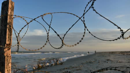 Fence with barbed wire on background of sea