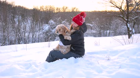 Young woman sitting with her dog in snow outdoors