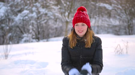 Girl in red hat and black coat outdoors.