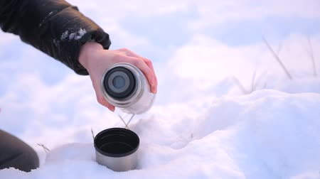 Metal flask close up with female hand in snow