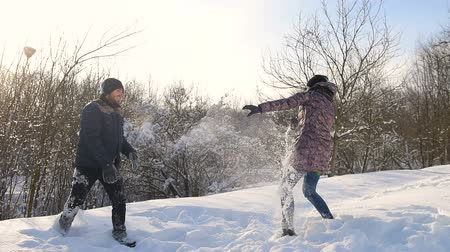 Couple snowball fighting at snowy park.