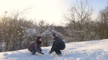 Young couple playing in snow at snowy park.