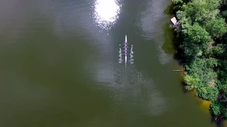 Drone follow four crew rowers in a boat on river