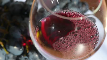Pour wine in glass with grape close up