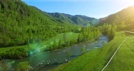 долина : UHD 4K aerial view. Low flight over fresh cold mountain river, meadow and road at sunny summer morning. Стоковые видеозаписи