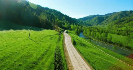 aktywność : Aerial UHD 4K view. Low air flight over mountain rural dirt road and meadow.
