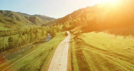 manzaraları : Aerial UHD 4K view. Low air flight over mountain rural dirt road and meadow at sunny summer morning