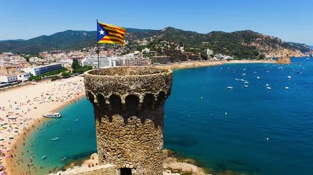 pearl : Aerial view of an old architectural building with tourists on the beach and yachts in harbor. The national flag is waving on the castle. Spain, Catalonia, Castell de Tossa