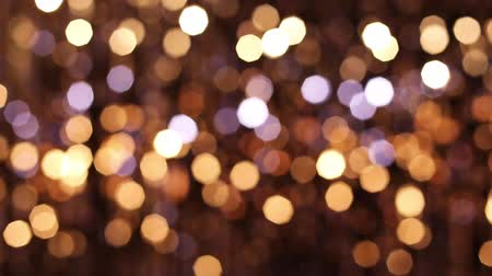 doted : Abstract glittering lights, gold background, a real shot in the video blur